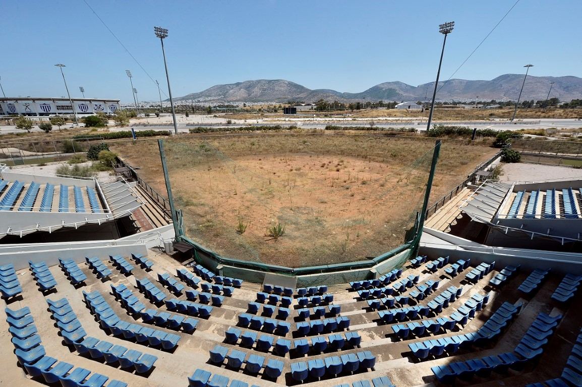 "ATHENS, GREECE - JULY 31: General view of the Olympic Softball stadium at the Helliniko Olympic complex in Athens, Greece on July 31, 2014. Ten years ago the XXVIII Olympiad was held in Athens from the 13th - 29th August with the motto ""Welcome Home"". The cost of hosting the games was estimated to be approx 9 billion euros with the majority of sporting venues built specifically for the games. Due to Greece's economic frailties post Olympic Games there has been no further investment and the majority of the newly constructed stadiums now lie abandoned. (Photo by Milos Bicanski/Getty Images)"