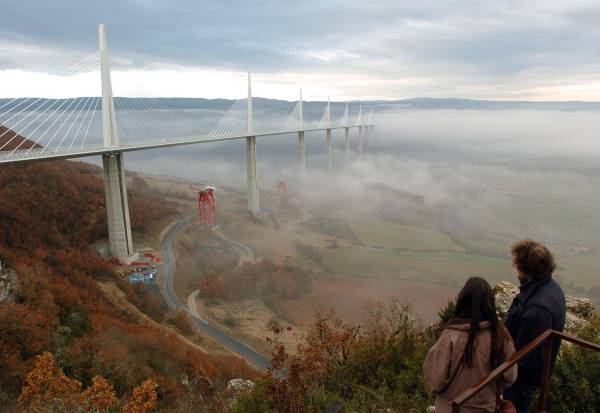 People look at the Millau bridge, the world's tallest traffic bridge, Thursday, Dec. 9, 2004, in Millau, France. Construction workers have nearly completed work on the roadway of the bridge, a viaduct that soars over a valley in southern France. The bridge, reaching about 270 meters (890 feet) at its highest point, will be inaugurated by President Jacques Chirac on Dec. 14 and opens to traffic on Dec. 17. (AP Photo/Christophe Ena)